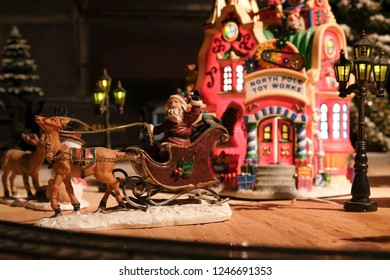 Toy figurines of Santa Clause in his sleigh with reindeer and toyshop in view. From an Christmas themed electric train set.