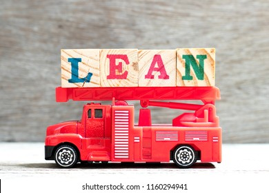 Toy fire ladder truck hold letter block in word lean on wood background