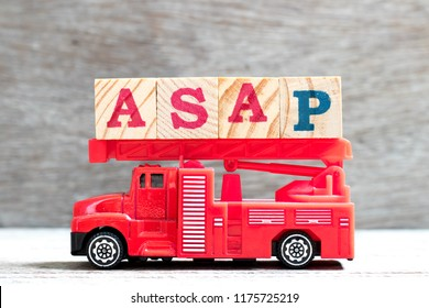 Toy fire ladder truck hold letter block in word ASAP (abbreviation of as soon as possible) on wood background