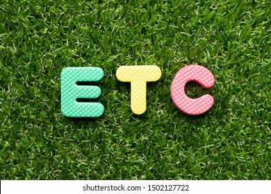 Toy foam letter in word etc (abbreviation of et cetera) on green grass background