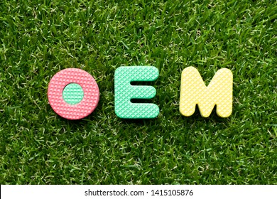 Toy foam letter in word OEM (Abbreviation of Original Equipment Manufacturer) on green grass background