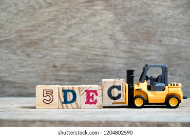 Toy forklift hold block c to complete word 5dec on wood background (Concept for calendar date 5 in month December)