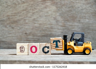 Toy forklift hold block T to complete word 9 oct on wood background (Concept for calendar date in month October)