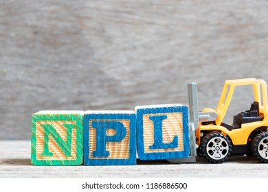 Toy forklift hold color letter block L to complete word  NPL (abbreviation of Non Performing Loan, Non-Patent Literature) on wood background