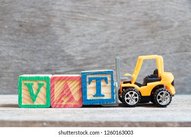 Toy forklift hold color letter block T to complete word VAT (Abberviation of Value added tax) on wood background