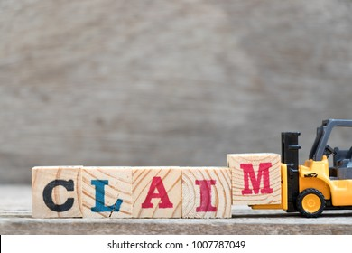 Toy forklift hold letter block M to complete word claim on wood background