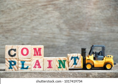 Toy forklift hold letter block T to complete word complaint on wood background