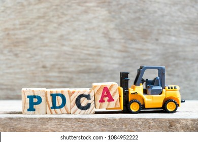 Toy forklift hold letter block A to complete word PDCA (Plan, Do, Check, Act) on wood background