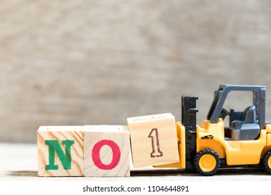 Toy forklift hold letter block 1 in word no1 on wood background (Concept of number onein game, competition, sport or business)