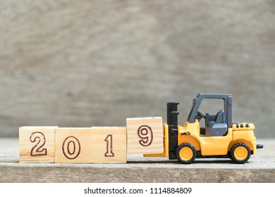 Toy forklift hold letter block 9 to complete word 2019 on wood background