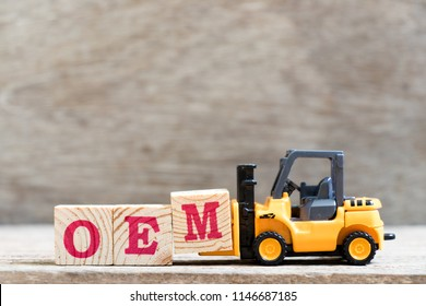 Toy forklift hold letter block M in word OEM (abbreviation of original equipment manufacturer) on wood background