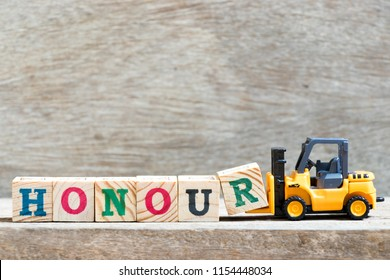 Toy forklift hold letter block r to complete word honour on wood background