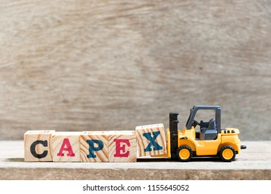 Toy forklift hold letter block X in word capex (abbreviation of capital expenditure) on wood background