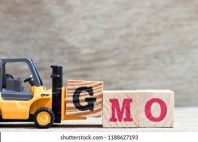 Toy forklift hold letter block G to complete word GMO (Abbreviation of Genetically Modified Organisms) on wood background