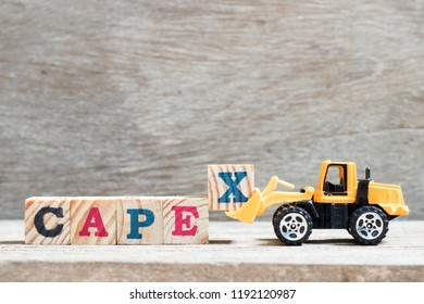 Toy forklift hold letter block x to complete word capex (abbreviation of capital expenditures) on wood background