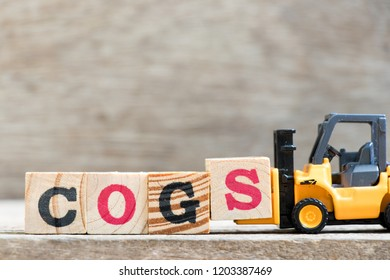 Toy forklift hold letter block S in word COGS (Abbreviation of Cost of goods sold) on wood background