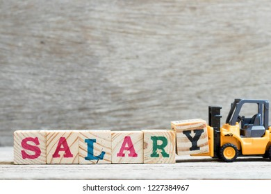 Toy forklift hold letter block y to complete word salary on wood background