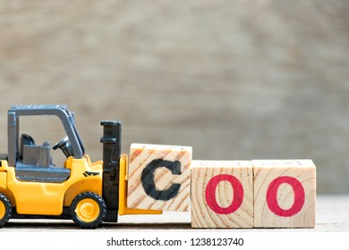 Toy forklift hold letter block c in word coo (abbreviation of chief operating officer) on wood background
