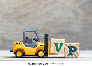 Toy forklift hold letter block V in word VP (abbreviation of vice president) on wood background