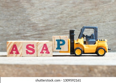 Toy forklift hold letter block p to complete word asap (abbreviation of as soon as possible) on wood background