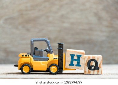 Toy forklift hold letter block H in word HQ (abbreviation of headquarter) on wood background