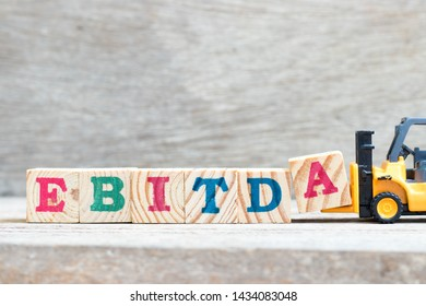 Toy forklift hold letter block A to complete word EBITDA (abbreviation of earnings before interest, taxes, depreciation and amortization) on wood background