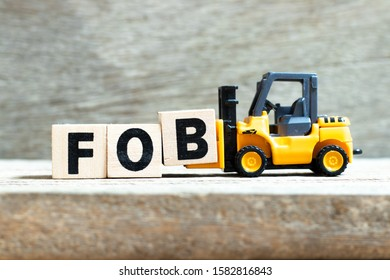 Toy forklift hold letter block B to complete word FOB (abbreviation of Free On Board) on wood background