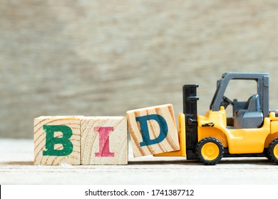 Toy forklift hold letter block d to complete word bid on wood background
