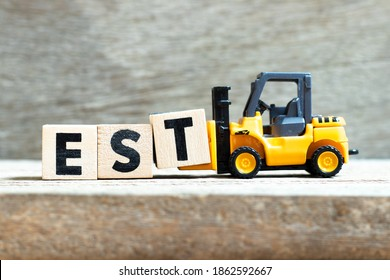 Toy forklift hold letter block t to complete word est (abbreviation of established, estimated, eastern time zone, expressed sequence tag) on wood background