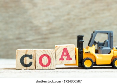 Toy forklift hold letter block a to complete word COA (abbreviation of certificate of analysis, certificate of authenticity, cause of action) on wood background