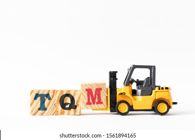 Toy forklift hold wood letter block M to complete word TQM (Abbreviation of total quality management) on white background