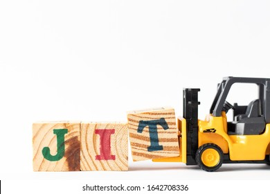 Toy forklift hold wood letter block T to complete word JIT (Abbreviation of Just in time) on white background