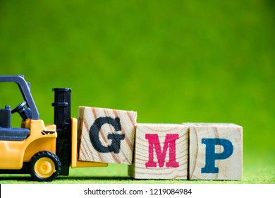 Toy forlift hold letter block G to fulfill word GMP (Abbreviation of Good Manufacturinc Practice) on green background