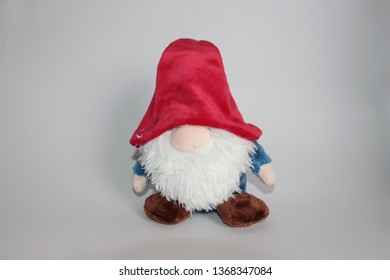 Toy in the form of a gnome doll on the gray background. Gnome with a thick white beard, wearing a red hat and blue clothes. Toys and dolls, Childhood and games concept.