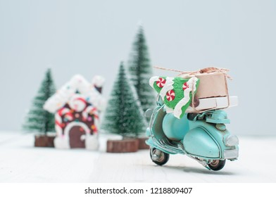 Toy gingerbread house where magic elves live in christmas trees town and motorbike with gifts