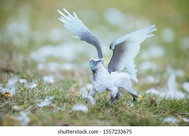Toy gryphon standing in feathers