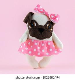 Toy handmade dog pug breed girl on pink background.