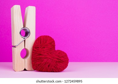 Toy heart and clothespin on pink background. Big wooden clothespin and red heart. St. Valentine's Day