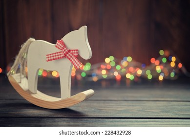 Toy horse with christmas lights on wooden background