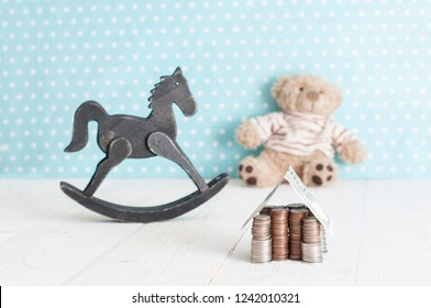 toy horse, teddy bear and money house in child's room. spending money on children.