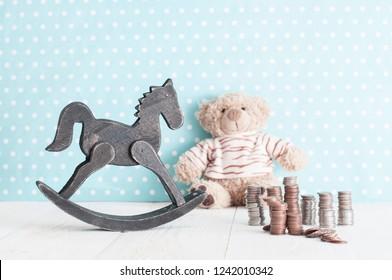 toy horse, teddy bear and money change in child's room. spending money on children.