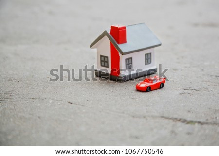 the toy house and the car on the ground