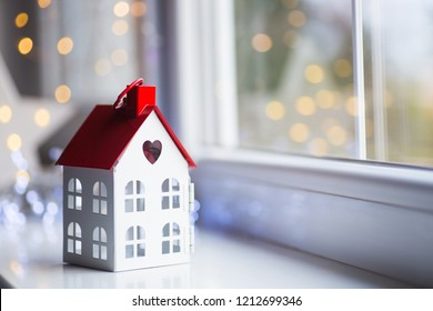 Toy house with hole in form of heart near window in daylight with garland lights on background. Romantic card. Valentine day banner.