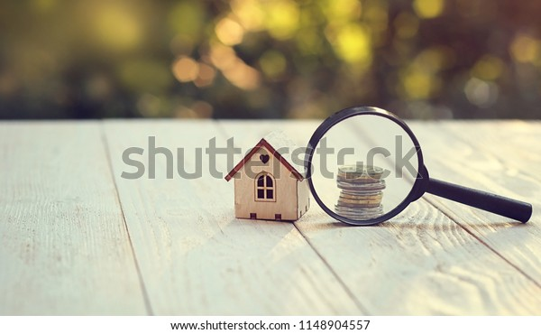 toy house, magnifying glass and coins. concept of mortgage, construction, rental housing. copy space
