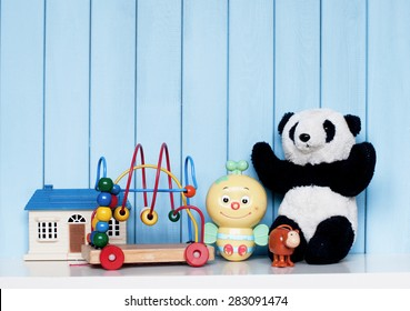 Toy house, old vintage panda, mechanical bee, clockwork monkey and spiral labyrinth on the bookshelf in the children's room on blue wooden background
