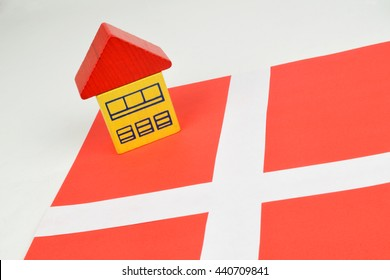 A toy house on a Danish flag to represent the Danish property market.