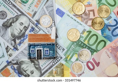 Toy house on many euro and dollar banknotes and euro coins- closeup shot