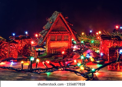 Toy house on a wooden background entwined Christmas garland, there are small gifts and branches of the Christmas tree. Beautiful Christmas background. Tinted photo