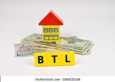A toy house sits on a pile of U.S. Dollars with a buy to let sign in the foreground. A metaphor on real estate investment.
