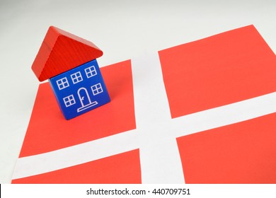 A toy house sitting on a Danish flag. A still life on Danish property.